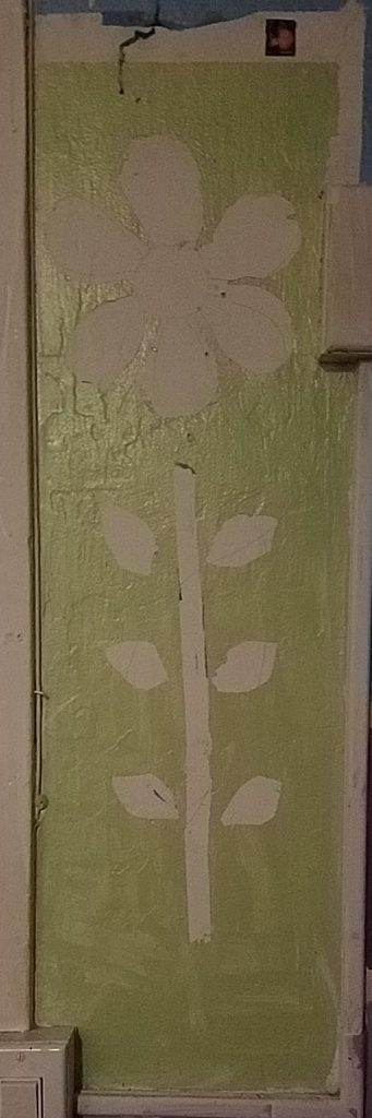A green background with the outline of an unfinished flower, that has some pencil sketches and remains of blue tape in the white negative space the flower should occupy.